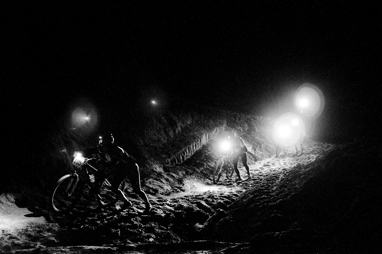 Riders push up the sandy hill in the dark or the 24 Hours of Moab endurance race.