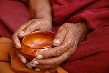 Hands of a Tibetan monk holding a wooden tea cup.  Lama Yuru, Ladakh, India